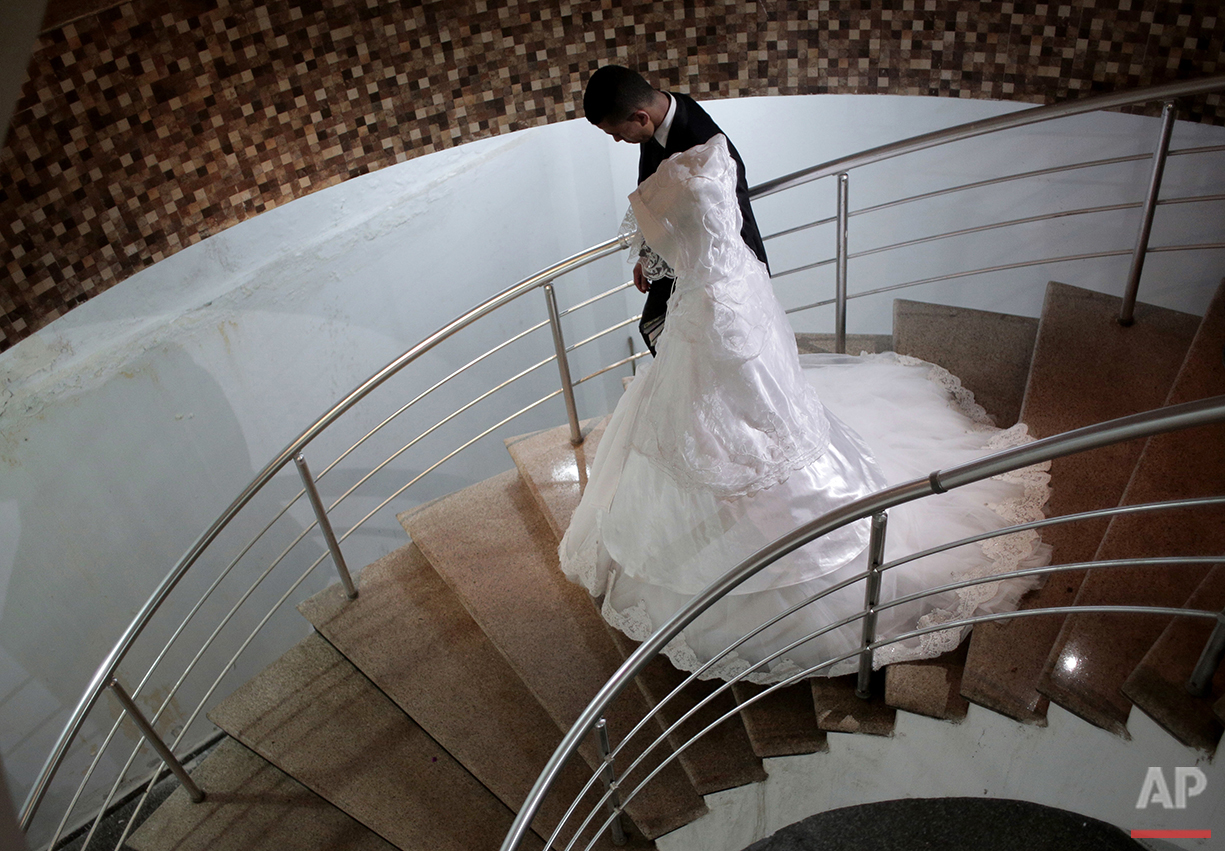 In this Saturday, July 31, 2016 photo, Palestinian groom Saed Abu Aser and his bride, Falasteen, take the stairs down to the wedding hall in Gaza City. (AP Photo/Khalil Hamra)