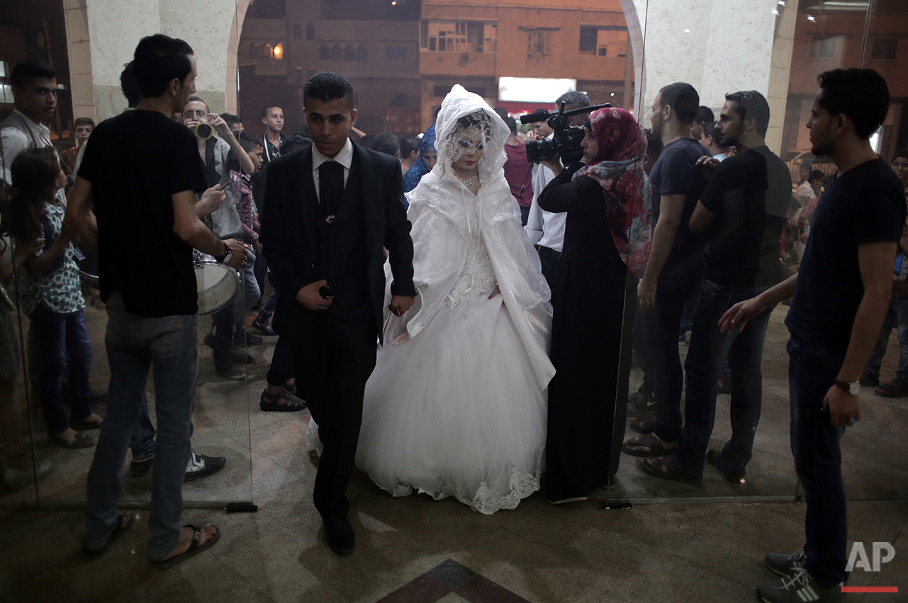 In this Saturday, July 30, 2016 photo, Palestinian groom Saed Abu Aser and his bride, Falasteen, walk into the wedding hall, in Gaza City. (AP Photo/ Khalil Hamra)