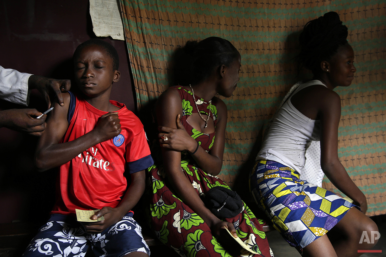 In this photo taken Thursday July 21, 2016, residents of the Kisenso district of Kinshasa, receive yellow fever vaccines. (AP Photo/Jerome Delay)