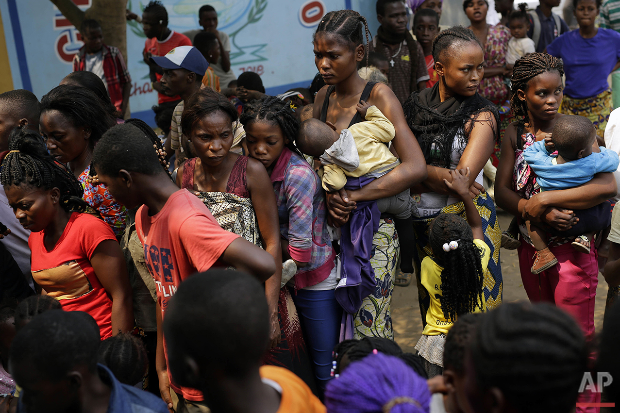 In this photo taken Thursday July 21, 2016, residents of the Kisenso district of Kinshasa, line up to receive a yellow fever vaccine. (AP Photo/Jerome Delay)