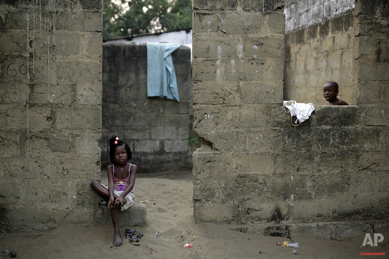 In this photo taken Wednesday July 20, 2016, children sit outside their home in the Kisenso district of Kinshasa, Democratic Republic of Congo. (AP Photo/Jerome Delay)