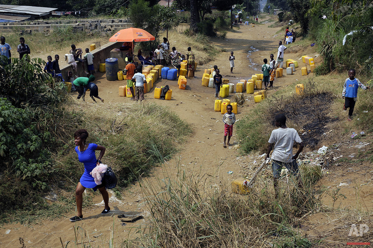 In this photo taken Wednesday July 20, 2016, residents of the Kisenso district of Kinshasa, Democratic Republic of Congo, gather at a water distribution point. (AP Photo/Jerome Delay)