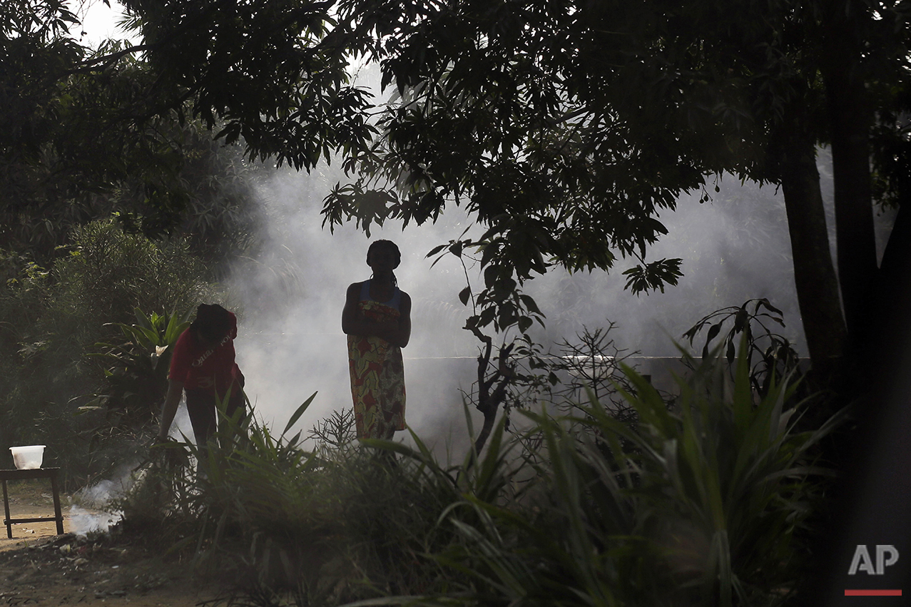 In this photo taken Wednesday July 20, 2016, residents of the Kisenso district of Kinshasa, Democratic Republic of Congo, stand by a smoking fire. (AP Photo/Jerome Delay)