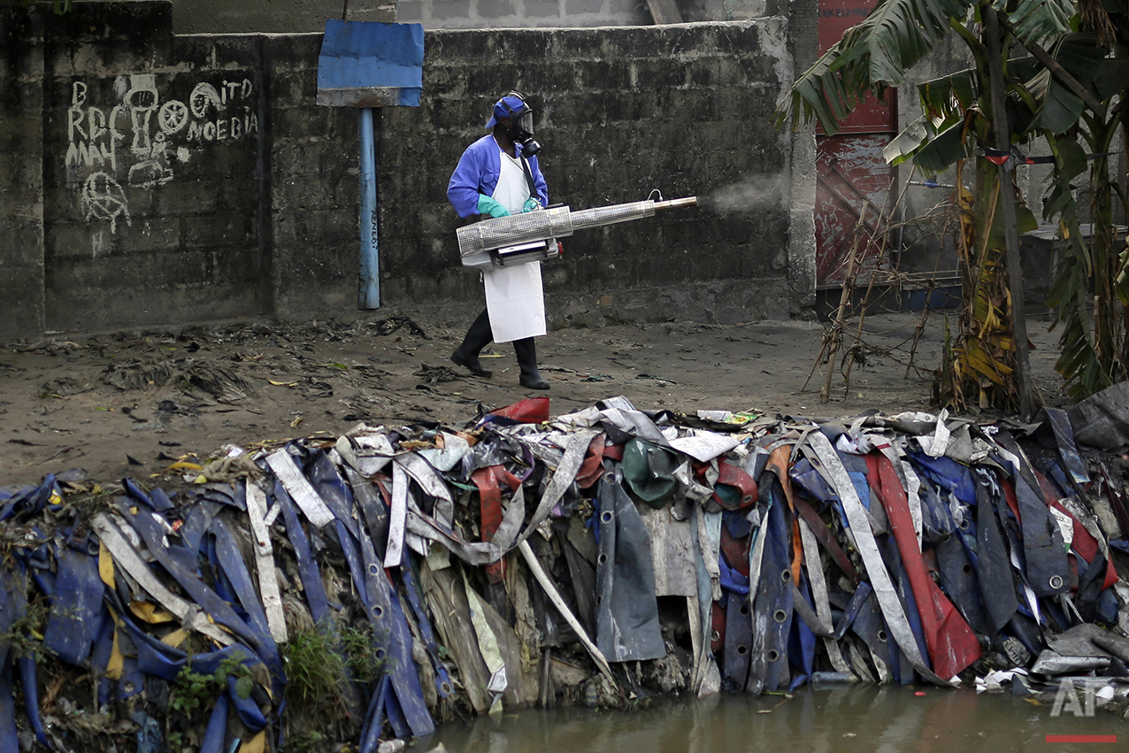 In this photo taken Friday July 22, 2016, teams from MSF carry out fumigation efforts in a bid to kill the mosquitos that transmit yellow fever. (AP Photo/Jerome Delay)