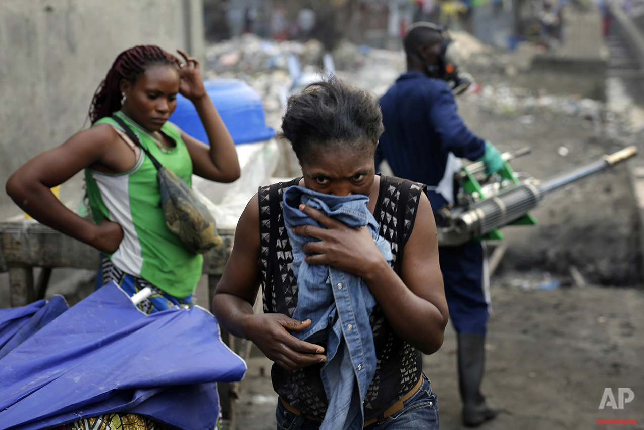 In this photo taken Friday July 22, 2016, residents of the Yolo Sud neighborhood of Kinshasa cover their faces as teams from MSF carry out fumigation efforts in a bid to kill the mosquitos that transmit yellow fever.  (AP Photo/Jerome Delay)