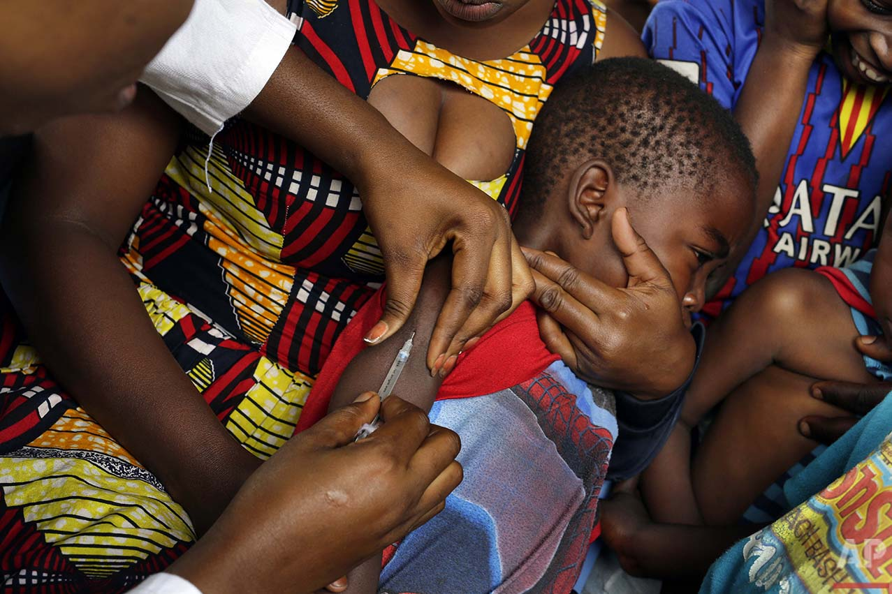 In this photo taken Thursday July 21, 2016, residents of the Kisenso district of Kinshasa,  receive yellow fever vaccines. Nearly 500,000 residents of the Kisenso neighborhood were set to be vaccinated as part of a campaign that was officially launched Wednesday. Some 66,000 were vaccinated on Thursday alone, according to Dr. Valentin Ndaye. The area has seen more than 80 suspected cases including four deaths since the beginning of the epidemic.(AP Photo/Jerome Delay)
