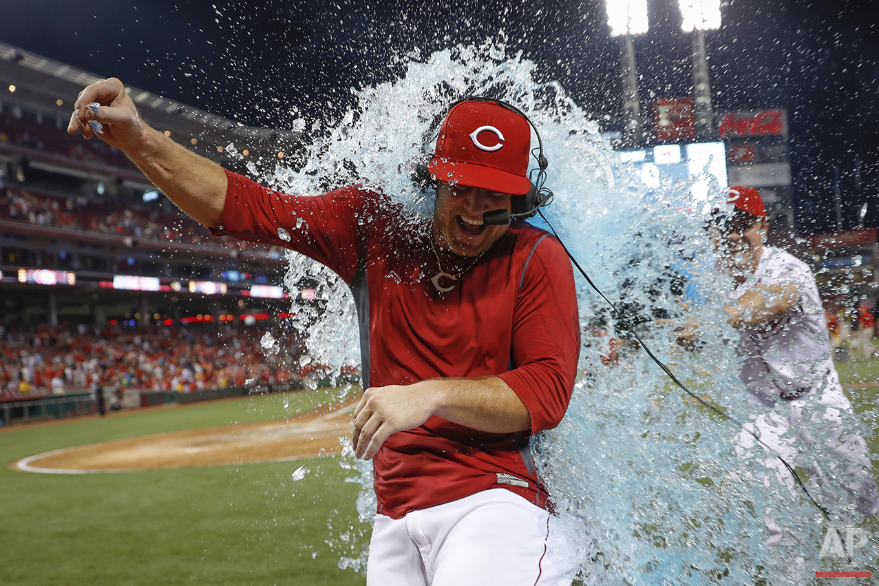 Cincinnati Reds' Scott Schebler is doused by Homer Bailey, right, after hitting a walk-off three run home run off St. Louis Cardinals relief pitcher Seung Hwan Oh during the ninth inning of a baseball game, Tuesday, Aug. 2, 2016, in Cincinnati. The Reds won 7-5. (AP Photo/John Minchillo)