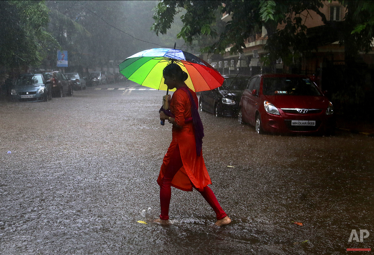 In this Friday, Aug. 5, 2016, photo, an Indian woman holds an umbrella and walks through the rain in Mumbai, India. Monsoon season in India begins in June and ends in October. (AP Photo/Rafiq Maqbool)
