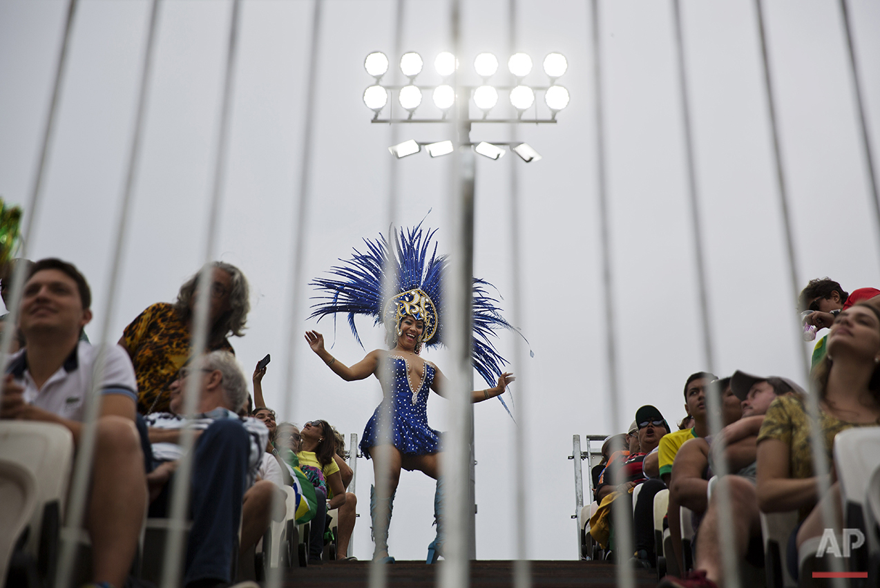 A samba dancer entertains the crowd during a break between action in a men's beach volleyball match at the 2016 Summer Olympics in Rio de Janeiro, Brazil, Monday, Aug. 8, 2016. (AP Photo/David Goldman)