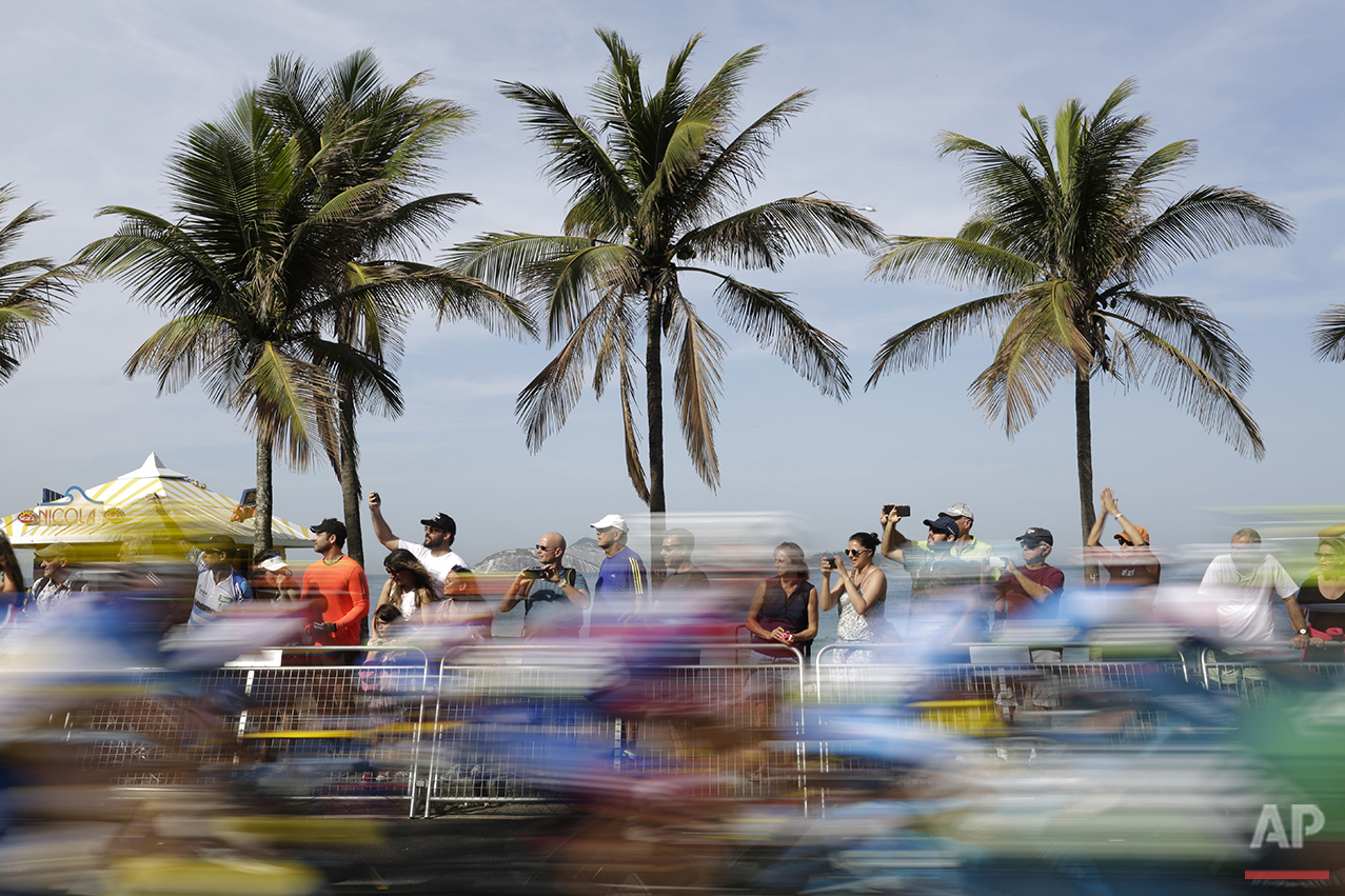 In this photo taken with a slow shutter speed, people watch as cyclists ride past them on Ipanema beach during the men's cycling road race final at the 2016 Summer Olympics in Rio de Janeiro, Brazil, Saturday, Aug. 6, 2016. (AP Photo/Felipe Dana)