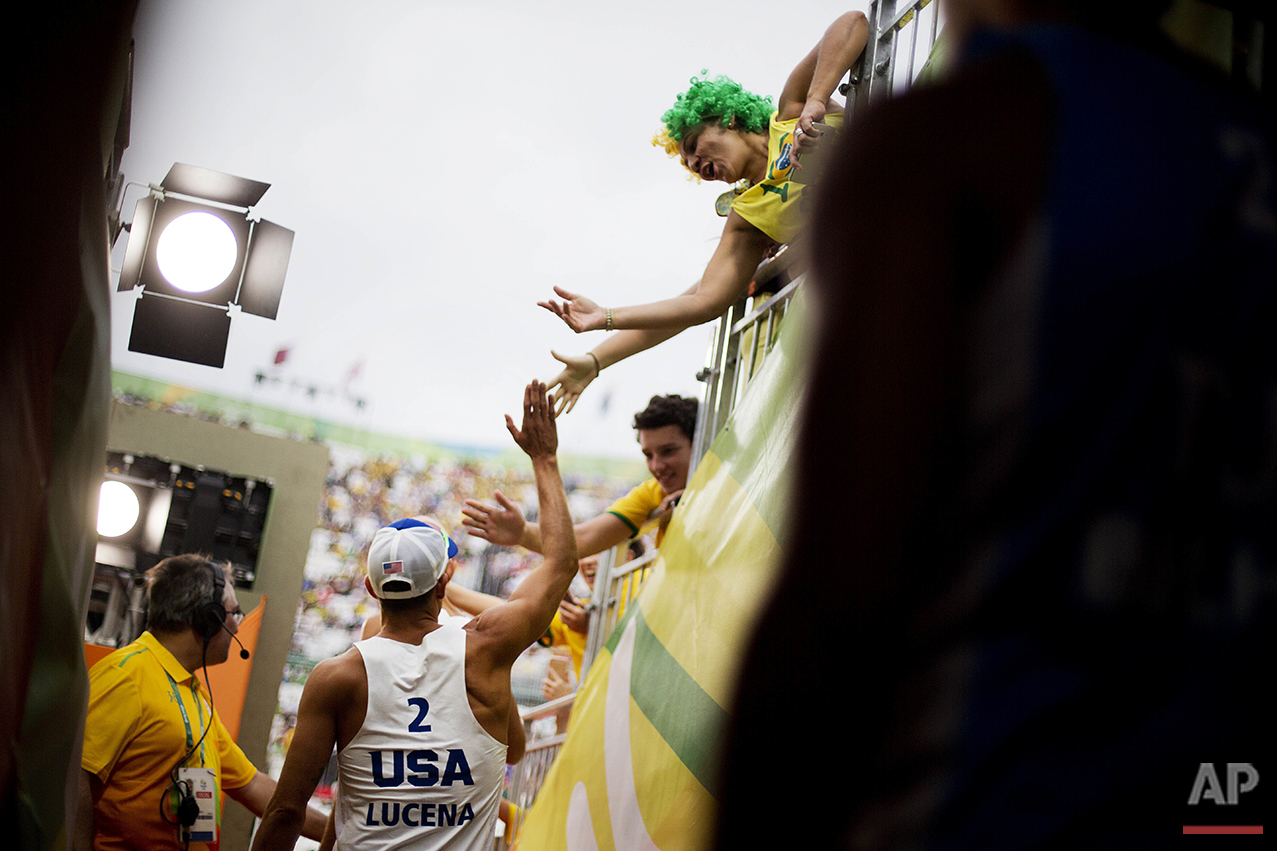 Nicholas Lucena, of the United States, high-fives fans as he takes the court with teammate Philip Dalhausser to play Tunisia in a men's beach volleyball match at the 2016 Summer Olympics in Rio de Janeiro, Brazil, Sunday, Aug. 7, 2016. (AP Photo/David Goldman)