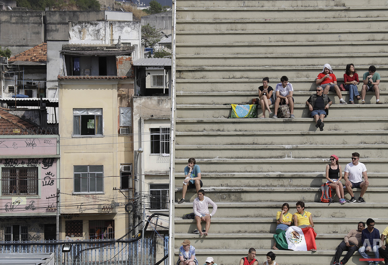 People watch an elimination round of the men's individual archery competition at the Sambadrome venue, located in a residential area, at the Summer Olympics in Rio de Janeiro, Brazil, Monday, Aug. 8, 2016. Spectators below hold Mexico's national flag. (AP Photo/Alessandra Tarantino)