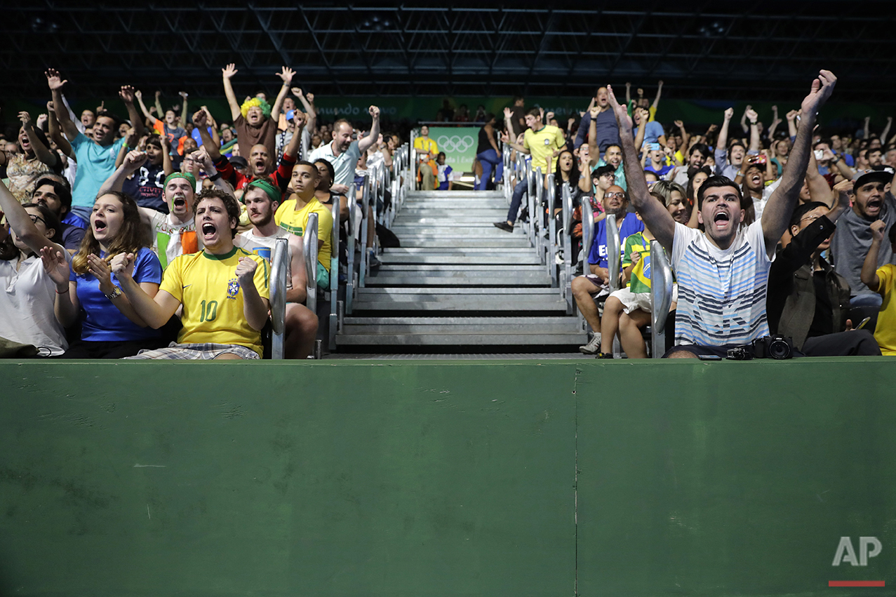 Brazilian fans cheer as they watch Hugo Calderano's table tennis match against Jun Mizutani, of Japan, at the 2016 Summer Olympics in Rio de Janeiro, Brazil, Monday, Aug. 8, 2016. (AP Photo/Jae C. Hong)