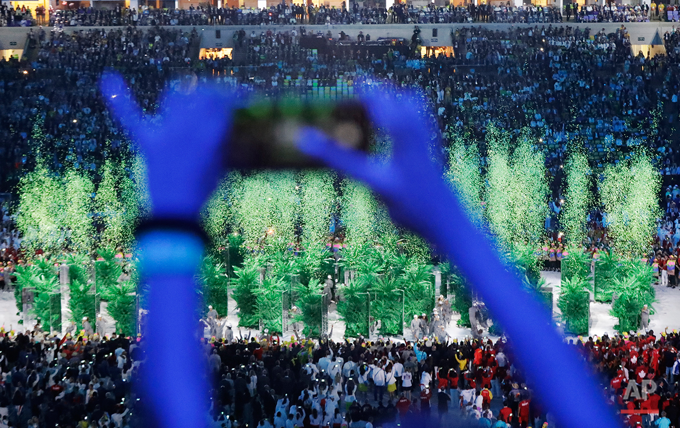 An audience member takes a picture during the opening ceremony for the 2016 Summer Olympics in Rio de Janeiro, Brazil, Friday, Aug. 5, 2016. (AP Photo/Robert F. Bukaty)