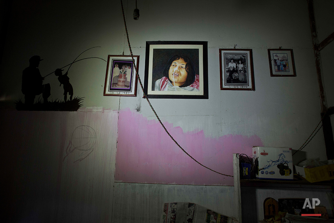 A portrait of Irom Sharmila, center, hangs on a wall with other family photographs at her home in Imphal, northeastern Manipur state, India, Monday, Aug.8, 2016. The 44-year-old activist who has been on a hunger strike for nearly 16 years to protest alleged brutality by India's military is expected to end her fast on Aug. 9. (AP Photo/Anupam Nath)