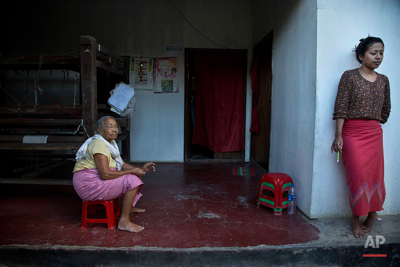 Irom Sakhi Devi, 84, mother of Irom Sharmila, sits as Irom Sunibala, 27, an air hostess and niece of Irom Sharmila who has arrived to meet Sharmila on Tuesday stands at her home in Imphal, northeastern Manipur state, India, Monday, Aug.8, 2016.  Sharmila, the 44-year-old activist who has been on a hunger strike for nearly 16 years to protest alleged brutality by India's military is expected to end her fast on Tuesday, Aug. 9. (AP Photo/Anupam Nath)