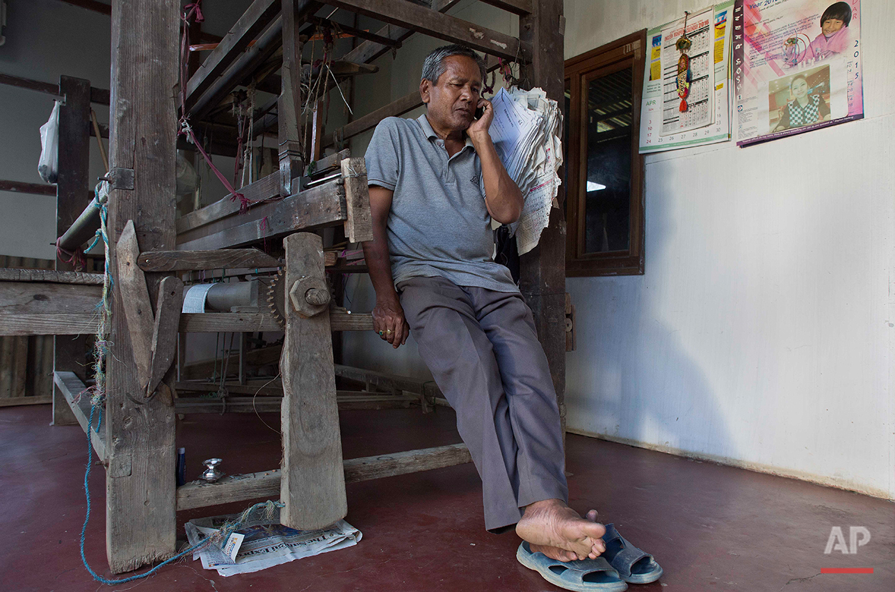 Singhjit Singh, 58, elder brother of Irom Sharmila talks on a mobile phone to a foreign media at her home in Imphal, northeastern Manipur state, India, Monday, Aug.8, 2016. Sharmila, the 44-year-old activist who has been on a hunger strike for nearly 16 years to protest alleged brutality by India's military is expected to end her fast on Aug. 9. (AP Photo/Anupam Nath)
