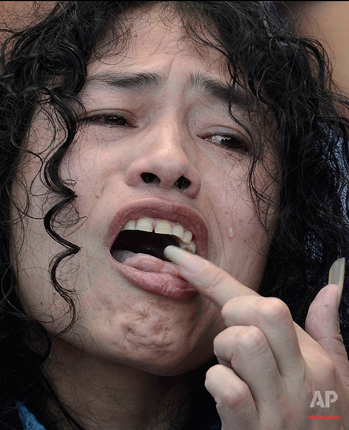 """Indian political activist Irom Sharmila licks honey from her hand to break her fast in Imphal, north-eastern Indian state of Manipur, India, Tuesday, Aug. 9, 2016. One of India's most prominent political activists ended a 16-year hunger strike Tuesday, licking honey from her hand and declaring """"I will never forget this moment."""" Sharmila had been force-fed through a tube in her nose and held by police since November 2000, when she began her fast to protest a draconian security law that gives immense power to security forces in the northeastern state of Manipur. (AP Photo/Anupam Nath)"""
