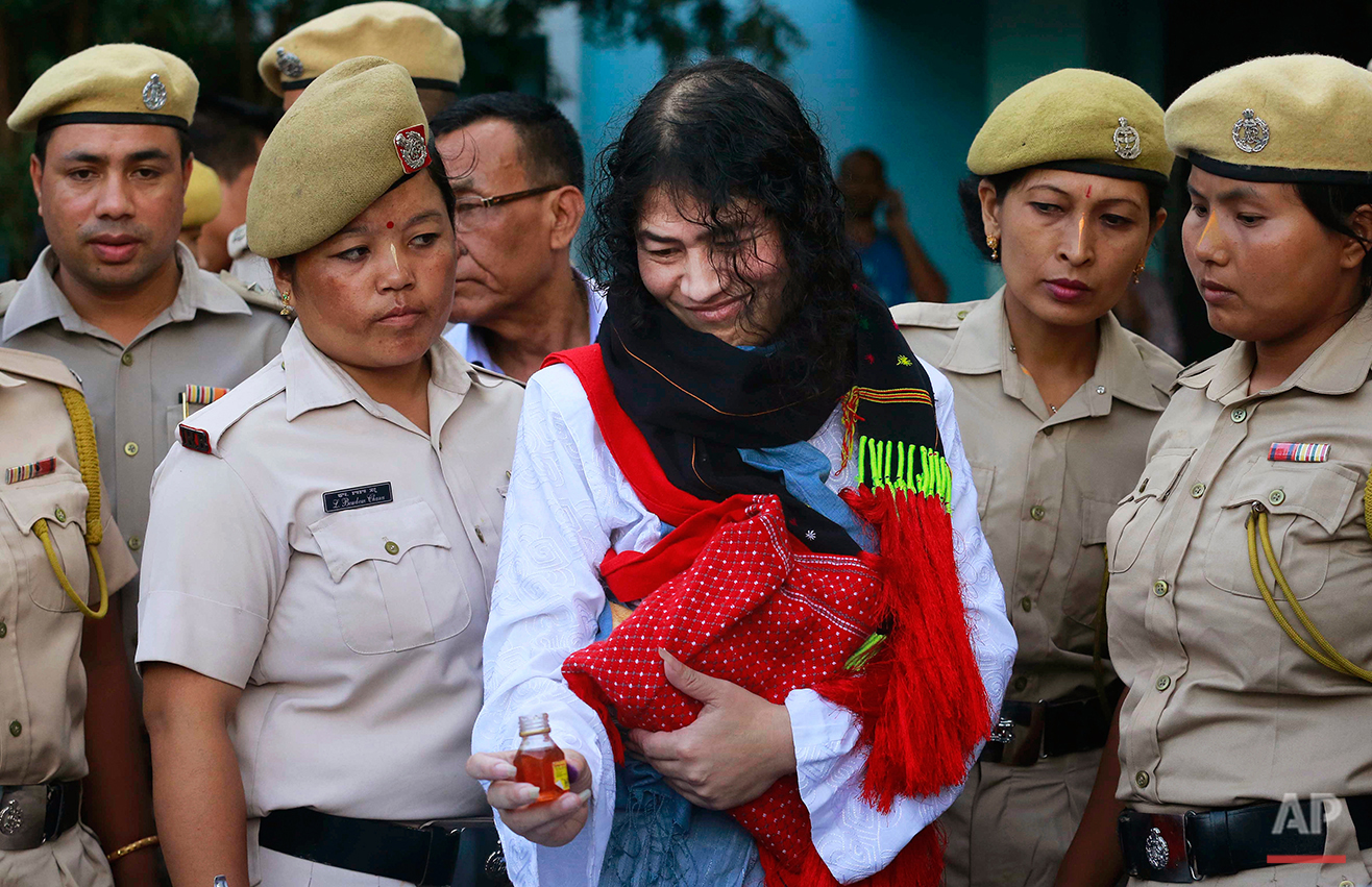 """Indian political activist Irom Sharmila picks up a bottle of honey to break her fast in Imphal, north-eastern Indian state of Manipur, India, Tuesday, Aug. 9, 2016. One of India's most prominent political activists ended a 16-year hunger strike Tuesday, licking honey from her hand and declaring """"I will never forget this moment."""" Sharmila had been force-fed through a tube in her nose and held by police since November 2000, when she began her fast to protest a draconian security law that gives immense power to security forces in the northeastern state of Manipur. (AP Photo/Anupam Nath)"""