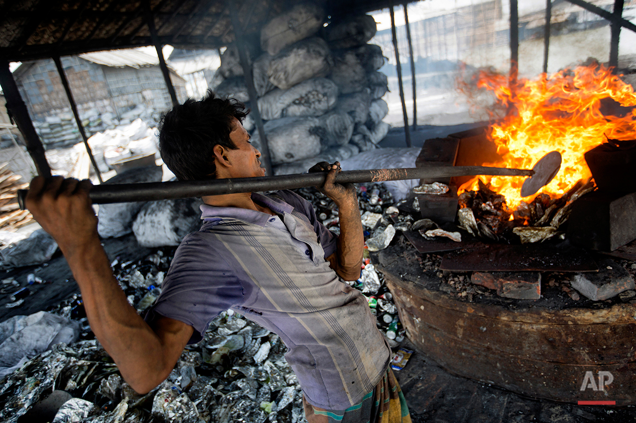In this Aug. 3, 2016 photo, Mohammad Jamal melts used aluminum waste at a recycling factory on the outskirts of Dhaka, Bangladesh. A large swath of land not far from the Buriganga River is dotted with makeshift tents that are home to men and women who travel far from home to work 12 hours a day recycling cans, industrial ash and medicine blister packets into raw aluminum.The work is difficult and dangerous. The workers have no safety equipment or masks to protect themselves from the fumes and aluminum dust.(AP Photo/A.M. Ahad)