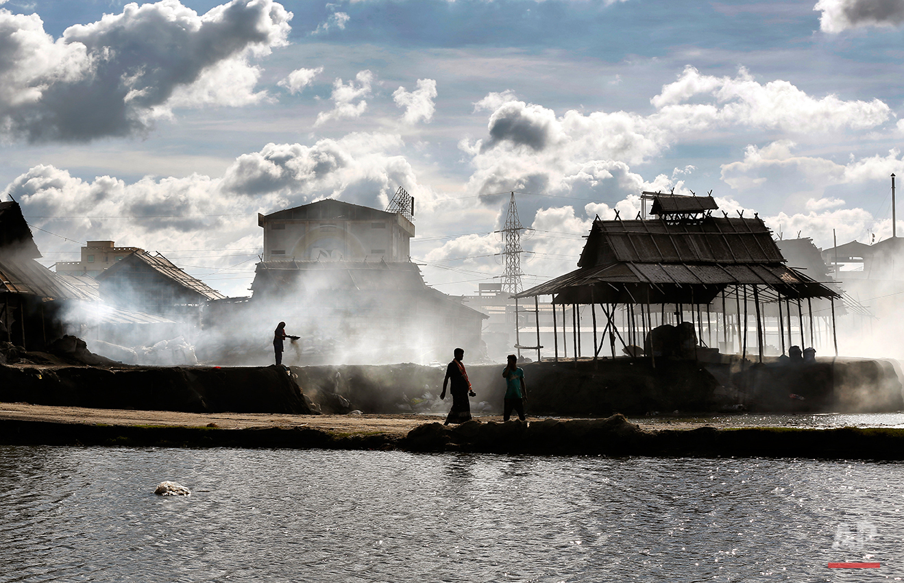 In this Aug. 3, 2016 photo, a Bangladeshi woman stands in rising smoke as she sorts aluminum pieces from industrial waste on the outskirts of Dhaka, Bangladesh. A large swath of land not far from the Buriganga River is dotted with makeshift tents that are home to men and women who travel far from home to work 12 hours a day recycling cans, industrial ash and medicine blister packets into raw aluminum. The work is difficult and dangerous. The workers have no safety equipment or masks to protect themselves from the fumes and aluminum dust. (AP Photo/ A.M. Ahad)