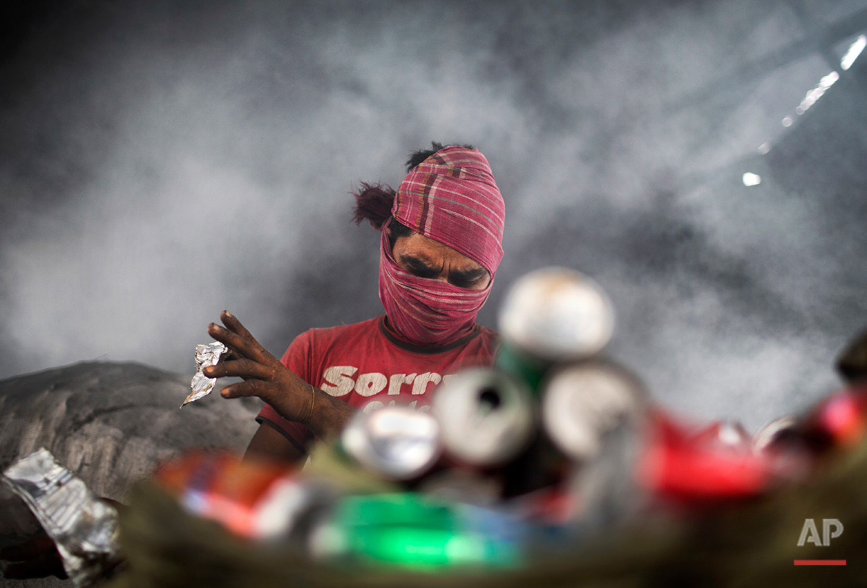 In this Aug. 3, 2016 photo, Mohammad Mosharrof sorts aluminum pieces from industrial waste, in the outskirts of Dhaka, Bangladesh. A large swath of land not far from the Buriganga River is dotted with makeshift tents that are home to men and women who travel far from home to work 12 hours a day recycling cans, industrial ash and medicine blister packets into raw aluminum. The work is difficult and dangerous. The workers have no safety equipment or masks to protect themselves from the fumes and aluminum dust. (AP Photo/ A.M. Ahad)