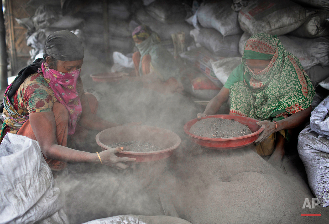In this Aug. 6, 2016 photo, Bangladeshi women sort aluminum pieces from industrial waste on the outskirts of Dhaka, Bangladesh. A large swath of land not far from the Buriganga River is dotted with makeshift tents that are home to men and women who travel far from home to work 12 hours a day recycling cans, industrial ash and medicine blister packets into raw aluminum.The work is difficult and dangerous. The workers have no safety equipment or masks to protect themselves from the fumes and aluminum dust.(AP Photo/A.M. Ahad)