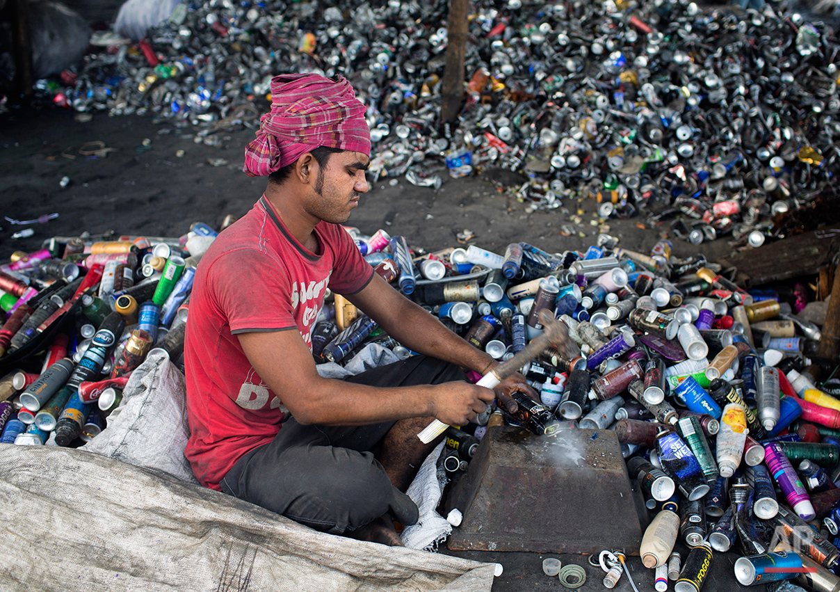 In this Aug. 3, 2016 photo, Mohammad Mosharrof sorts aluminum pieces from industrial waste on the outskirts of Dhaka, Bangladesh. A large swath of land not far from the Buriganga River is dotted with makeshift tents that are home to men and women who travel far from home to work 12 hours a day recycling cans, industrial ash and medicine blister packets into raw aluminum.The work is difficult and dangerous. The workers have no safety equipment or masks to protect themselves from the fumes and aluminum dust.(AP Photo/ A.M. Ahad)