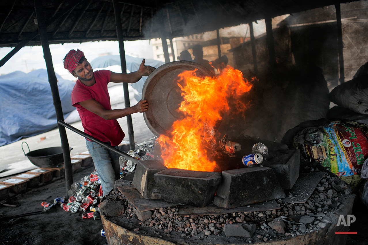 In this Aug. 3, 2016 photo, Monir Hossain melts recycled aluminum on the outskirts of Dhaka, Bangladesh. A large swath of land not far from the Buriganga River is dotted with makeshift tents that are home to men and women who travel far from home to work 12 hours a day recycling cans, industrial ash and medicine blister packets into raw aluminum.The work is difficult and dangerous. The workers have no safety equipment or masks to protect themselves from the fumes and aluminum dust.(AP Photo/A.M. Ahad)