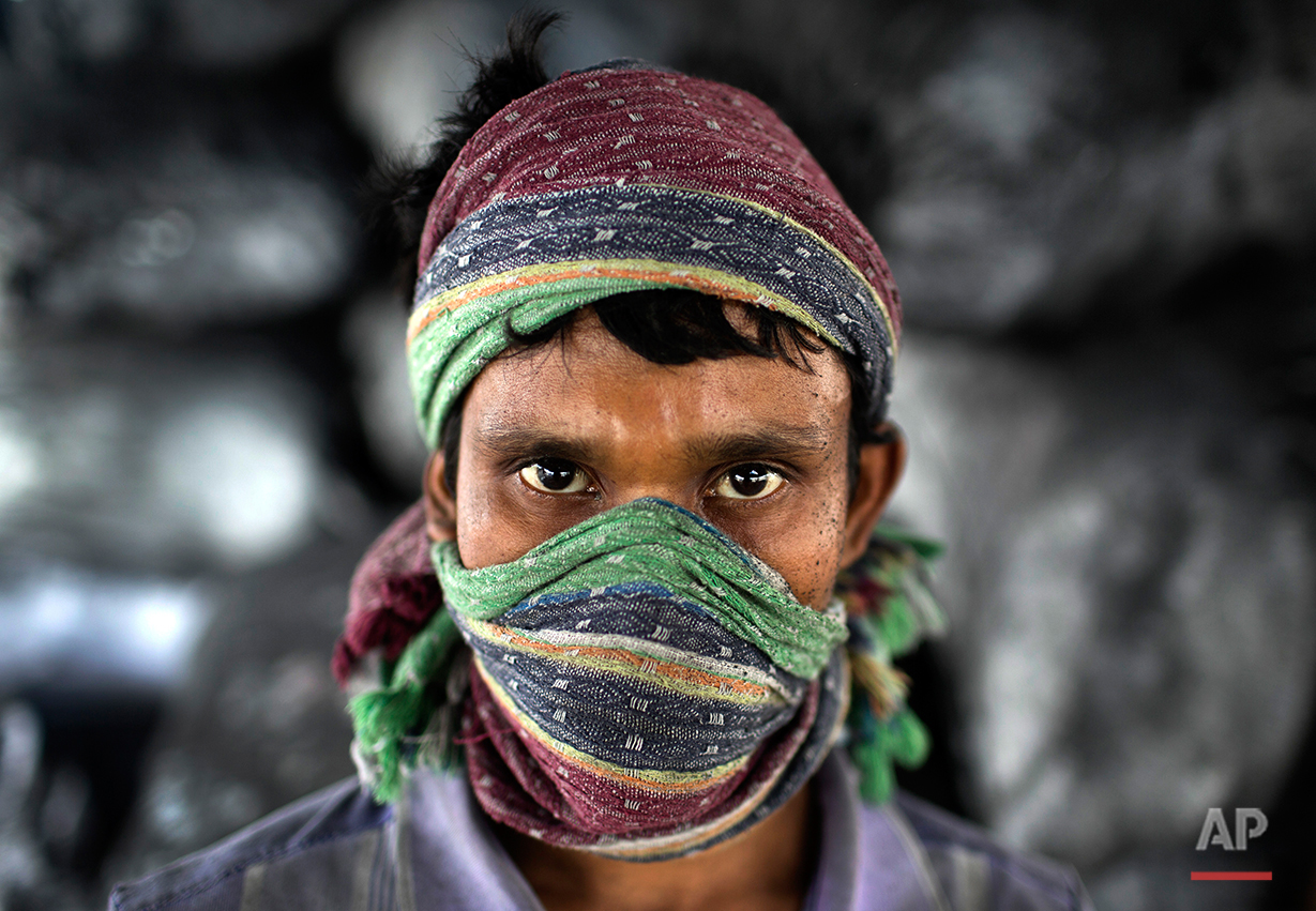 In this Aug. 3, 2016 photo, Mohammad Jamal poses for a portrait at an aluminum recycling factory on the outskirts of Dhaka, Bangladesh. A large swath of land not far from the Buriganga River is dotted with makeshift tents that are home to men and women who travel far from home to work 12 hours a day recycling cans, industrial ash and medicine blister packets into raw aluminum.The work is difficult and dangerous. The workers have no safety equipment or masks to protect themselves from the fumes and aluminum dust.(AP Photo/A.M. Ahad)