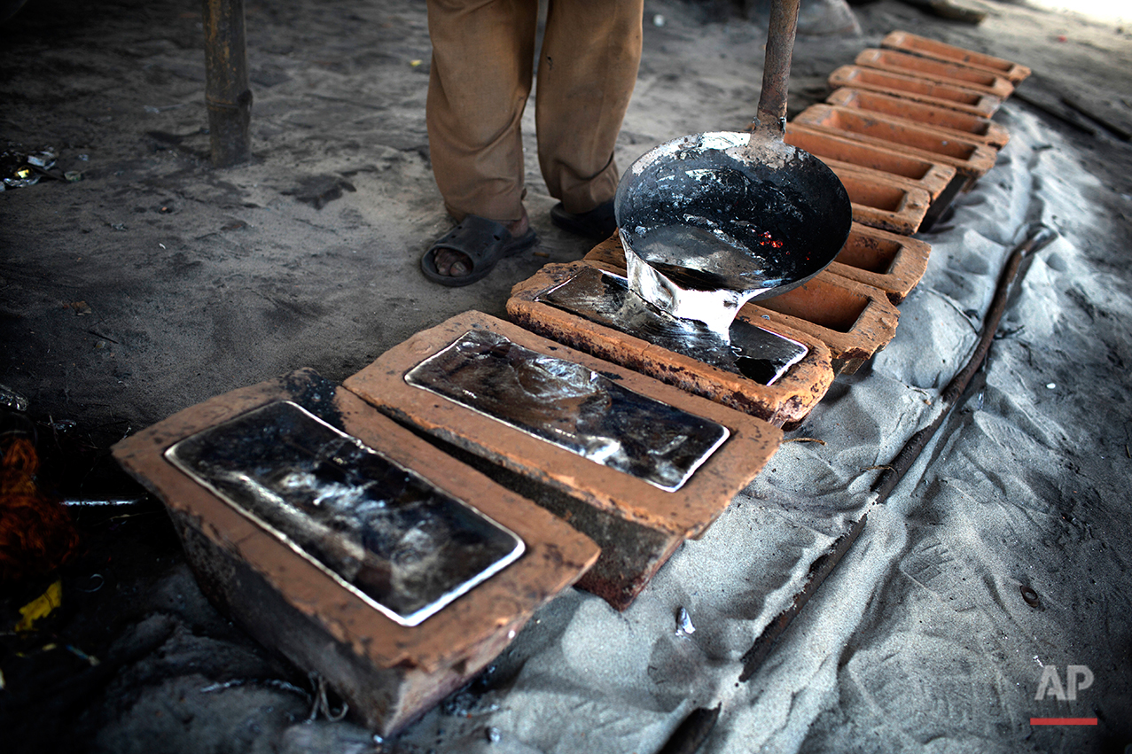 In this Aug. 3, 2016 photo, a worker pours liquid aluminum into casts at a recycling factory on the outskirts of Dhaka, Bangladesh. A large swath of land not far from the Buriganga River is dotted with makeshift tents that are home to men and women who travel far from home to work 12 hours a day recycling cans, industrial ash and medicine blister packets into raw aluminum.The work is difficult and dangerous. The workers have no safety equipment or masks to protect themselves from the fumes and aluminum dust.(AP Photo/A.M. Ahad)