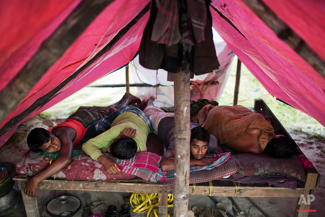In this Aug. 6, 2016 photo, workers rest under a tent they share near an aluminum recycling factory on the outskirts of Dhaka, Bangladesh. A large swath of land not far from the Buriganga River is dotted with makeshift tents that are home to men and women who travel far from home to work 12 hours a day recycling cans, industrial ash and medicine blister packets into raw aluminum. The work is difficult and dangerous. The workers have no safety equipment or masks to protect themselves from the fumes and aluminum dust. (AP Photo/ A.M. Ahad)