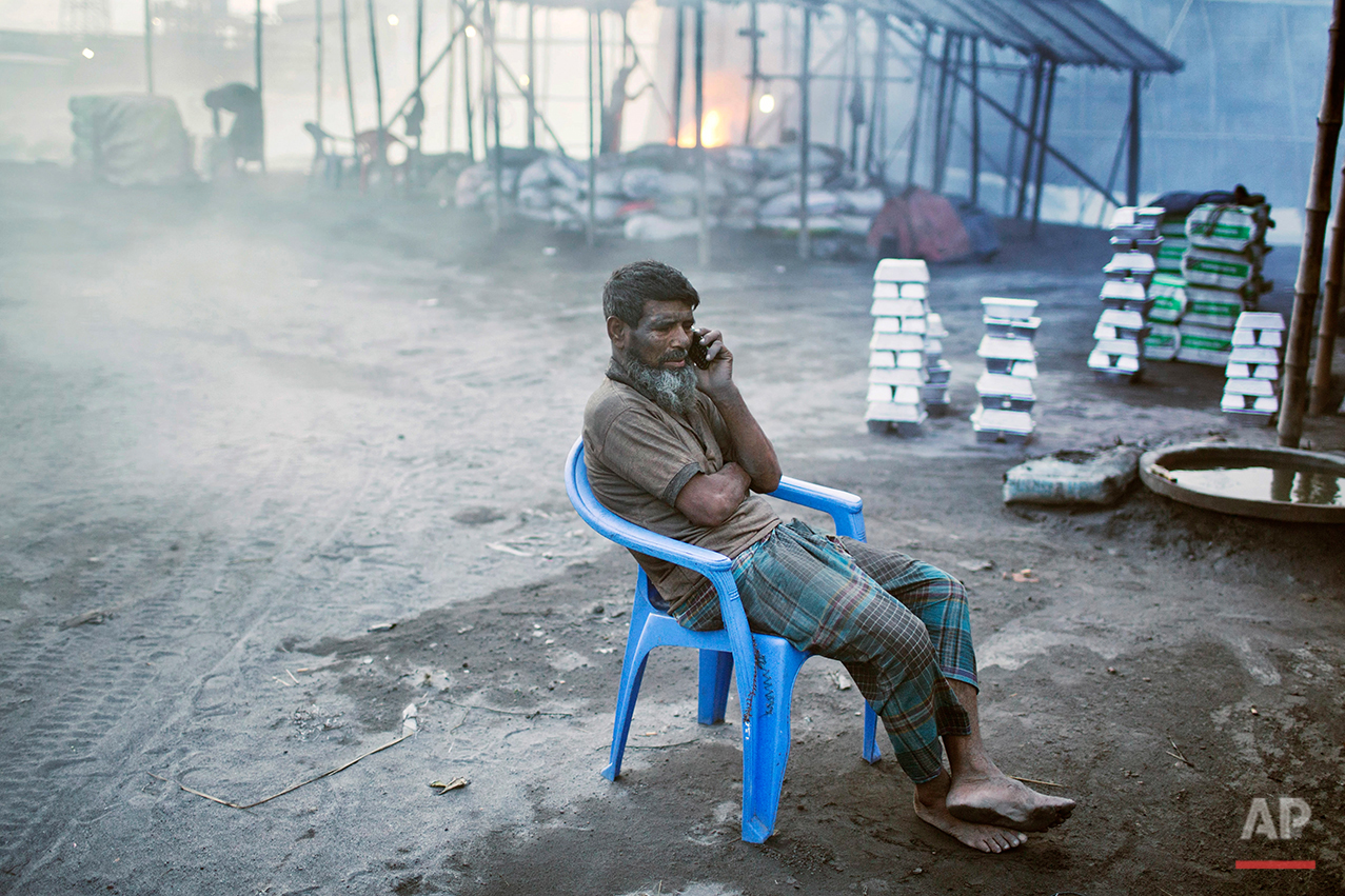 In this Aug. 6, 2016 photo, Mohammad Motaleb, an aluminum recycling factory worker, talks to his daughter during a break on the outskirts of Dhaka, Bangladesh. A large swath of land not far from the Buriganga River is dotted with makeshift tents that are home to men and women who travel far from home to work 12 hours a day recycling cans, industrial ash and medicine blister packets into raw aluminum. The work is difficult and dangerous. The workers have no safety equipment or masks to protect themselves from the fumes and aluminum dust. (AP Photo/ A.M. Ahad)