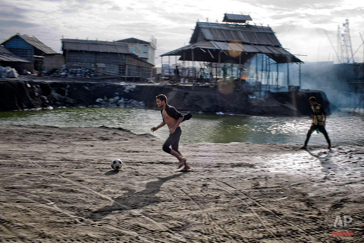In this Aug. 6, 2016 photo, aluminum recycling worker Rubel Hossain plays soccer near a recycling factory on the outskirts of Dhaka, Bangladesh. A large swath of land not far from the Buriganga River is dotted with makeshift tents that are home to men and women who travel far from home to work 12 hours a day recycling cans, industrial ash and medicine blister packets into raw aluminum. The work is difficult and dangerous. The workers have no safety equipment or masks to protect themselves from the fumes and aluminum dust. (AP Photo/ A.M. Ahad)
