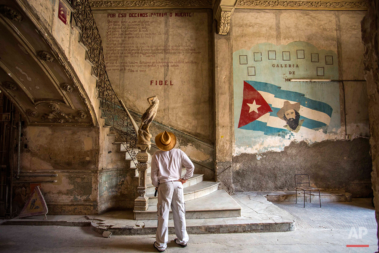 """A tourist looks at quote by Cuban Revolution leader Fidel Castro explaining in Spanish, 'Why we say homeland or death,"""" on a wall at the entrance of a landmark private restaurant  in Havana, Cuba, Thursday, July 28, 2016. After a decade out of the public eye, Fidel Castro has surged back in the run-up to his birthday next month as the inspiration for Cubans who want to maintain Communist orthodoxy in the face of mounting pressures to loosen control. (AP Photo/Desmond Boylan)"""
