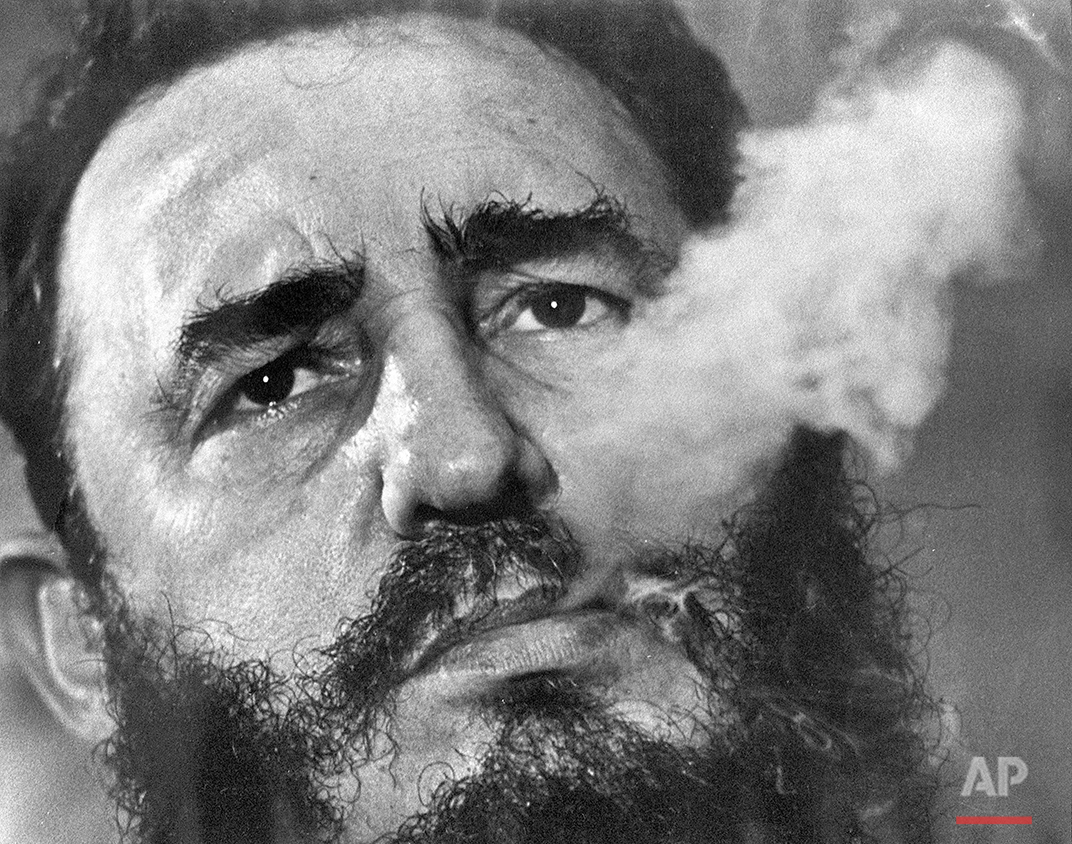 In this March 1985 photo, Cuban Prime Minister Fidel Castro exhales cigar smoke during an interview at his presidential palace in Havana, Cuba. Castro, a Havana attorney who fought for the poor, overthrew dictator Fulgencio Batista's government on Jan. 1, 1959. (AP Photo/ Charles Tasnadi)