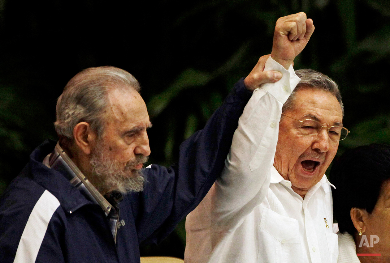 In this April 19, 2011 photo, Fidel Castro, left, raises his brother's hand, Cuba's President Raul Castro, center, as they sing the anthem of international socialism during the 6th Communist Party Congress in Havana, Cuba. As Fidel gets ready to celebrate his 90th birthday on Aug. 13, 2016, the leader of the Cuban revolution watched as his brother Raul granted Cubans new economic freedoms and declared detente with the United States after a half-century of hostility. (AP Photo/Javier Galeano)