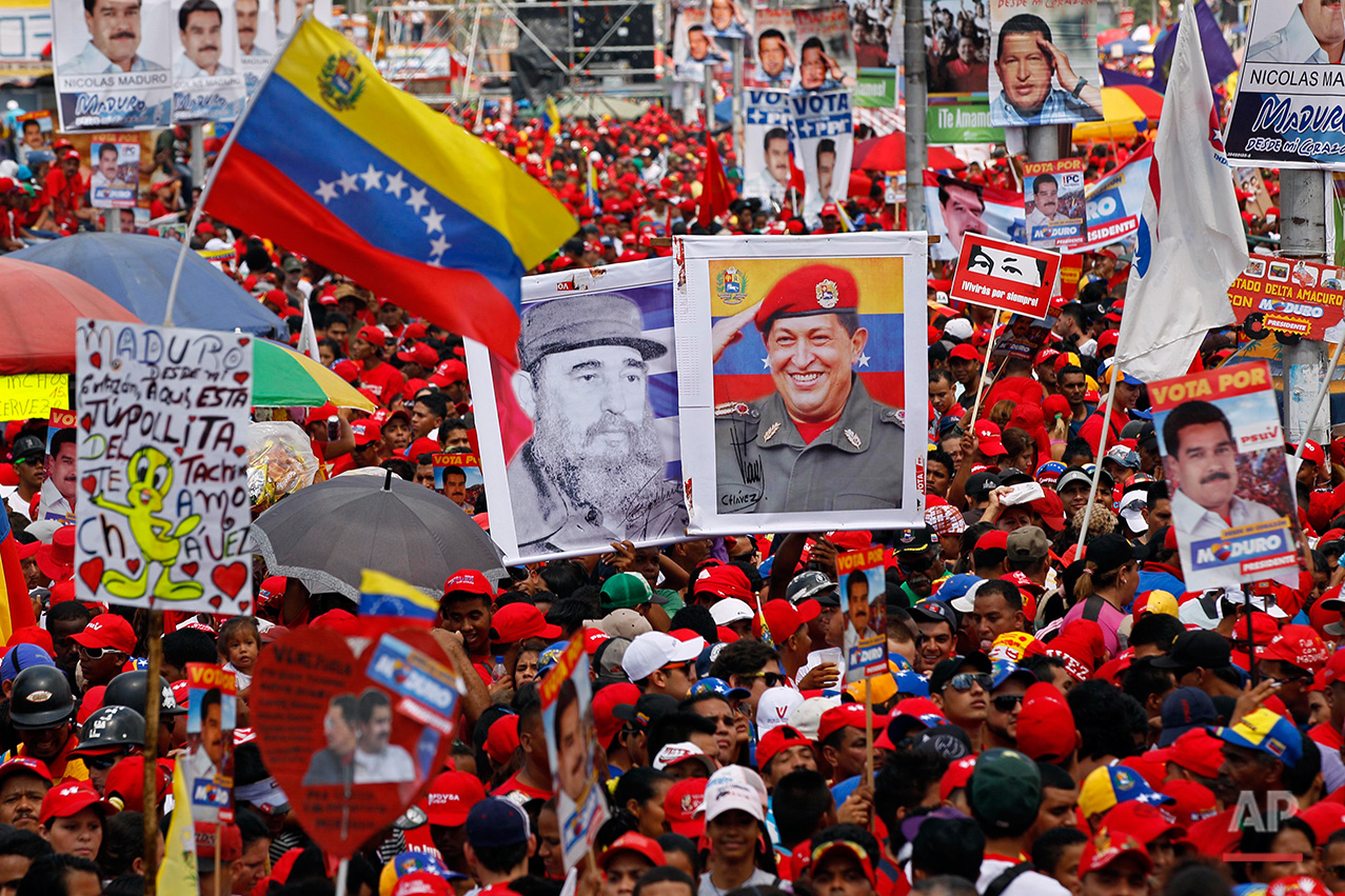 Holing images of Venezuela's late President Hugo Chavez, right, and Cuba's Fidel Castro, left, supporters attend the closing campaign rally for Venezuela's acting President Nicolas Maduro in Caracas, Venezuela, Thursday, April 11, 2013. (AP Photo/Ariana Cubillos)