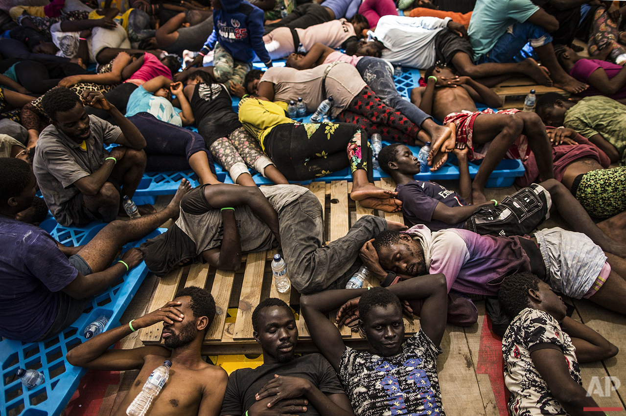 Migrants from Nigeria and the Ivory Coast rest on a vessel after being rescued by a Migrant Offshore Aid Station (MOAS) team in the central Mediterranean Sea, close to the Libyan territorial waters on Wednesday, Aug. 10, 2016. (AP Photo/Manu Brabo)
