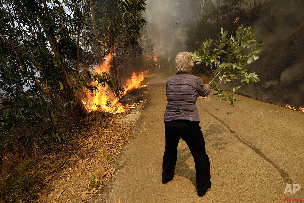 A woman uses a tree branch to fight a fire on a road leading to the village of Parada, northern Portugal, near Mortagua, on Thursday, Aug. 11 2016. Multiple blazes have been fed by brush in a hot, dry summer for several days. Major fires have also been raging in northwestern Spain and southern France. (AP Photo/Sergio Azenha)