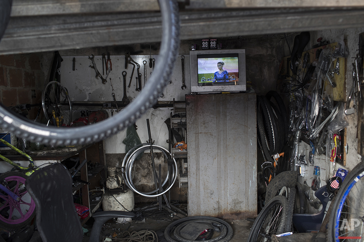 A television inside a bicycle repair shop shows the live transmission of Brazil's Jade Barbosa during the artistic gymnastics at the 2016 Summer Olympics in Rio de Janeiro, Brazil, Tuesday, Aug. 9, 2016. (AP Photo/Felipe Dana)