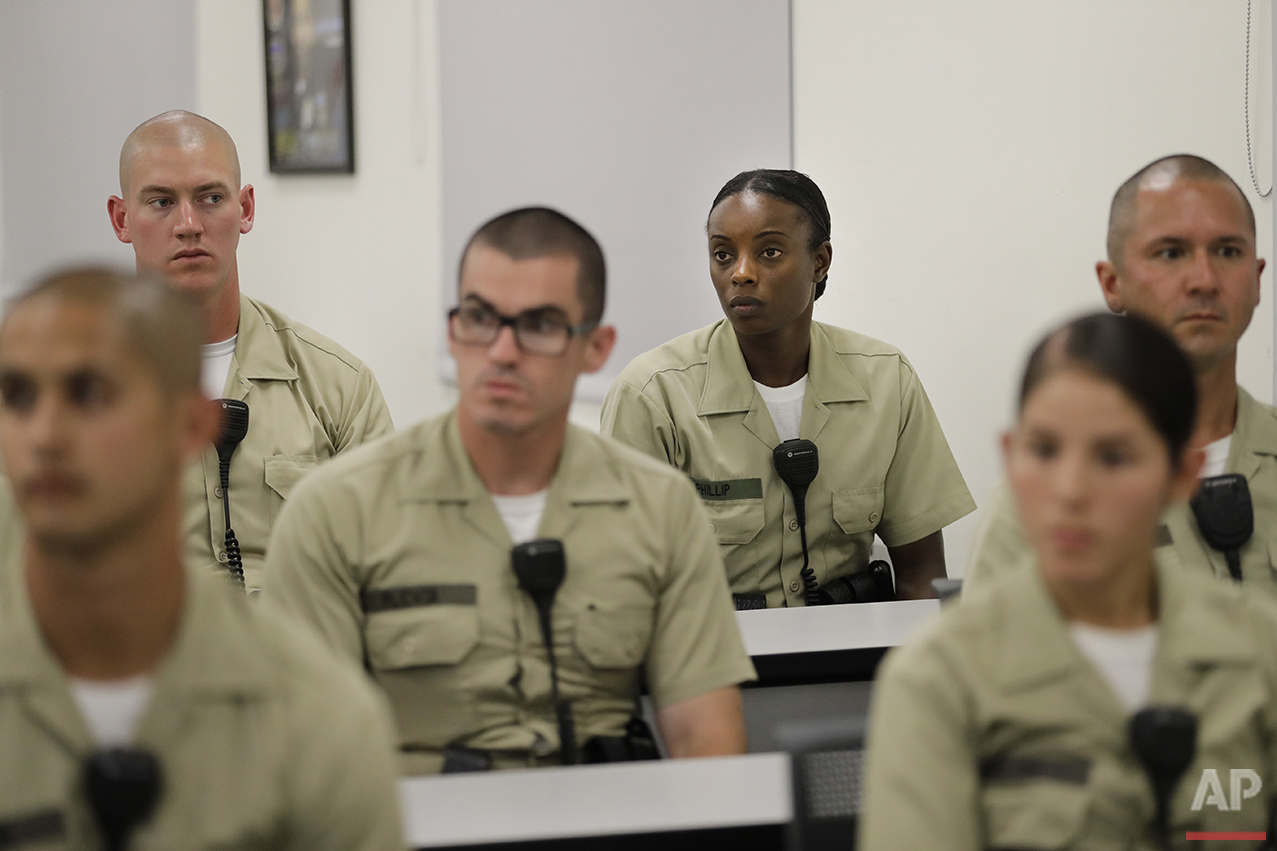 In this Tuesday, July 19, 2016 photo, Los Angeles County sheriff's deputy recruit Renata Phillip, third from right, listens to a lecture in a classroom at the Biscailuz Regional Training Center in Monterey Park, Calif. Phillip is one of just two black women in her class of 84 recruits. More than half are men and most are white or Hispanic. Only three recruits out of every 100 will make it to graduation, said Capt. Scott Gage, who's in charge of training at the Los Angeles County Sheriff's Department.  (AP Photo/Jae C. Hong)