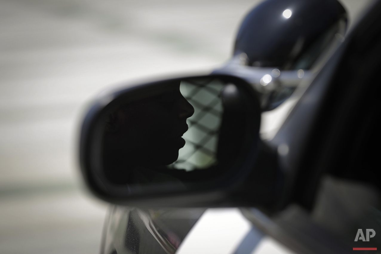 In this Tuesday, July 19, 2016 photo, Los Angeles County sheriff's deputy recruit Renata Phillip is reflected in a side mirror while sitting in a sheriff's vehicle during her training at the Biscailuz Regional Training Center in Monterey Park, Calif. (AP Photo/Jae C. Hong)