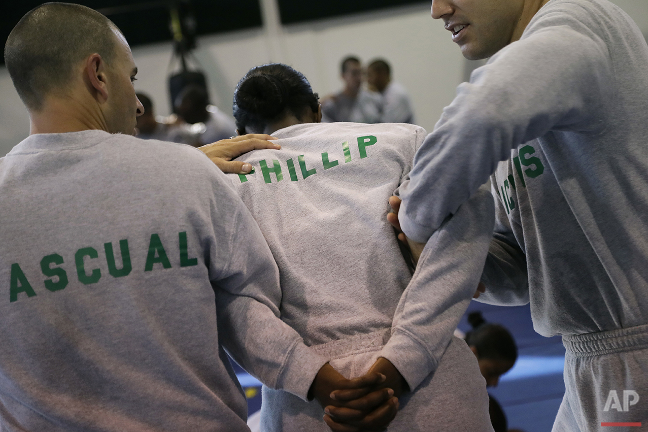 In this Friday, July 29, 2016 photo, Los Angeles County sheriff's deputy recruit Renata Phillip, center, trains with David Pascual, left, and Robert Nichols during a defensive tactics class at the Biscailuz Regional Training Center in Monterey Park, Calif. (AP Photo/Jae C. Hong)