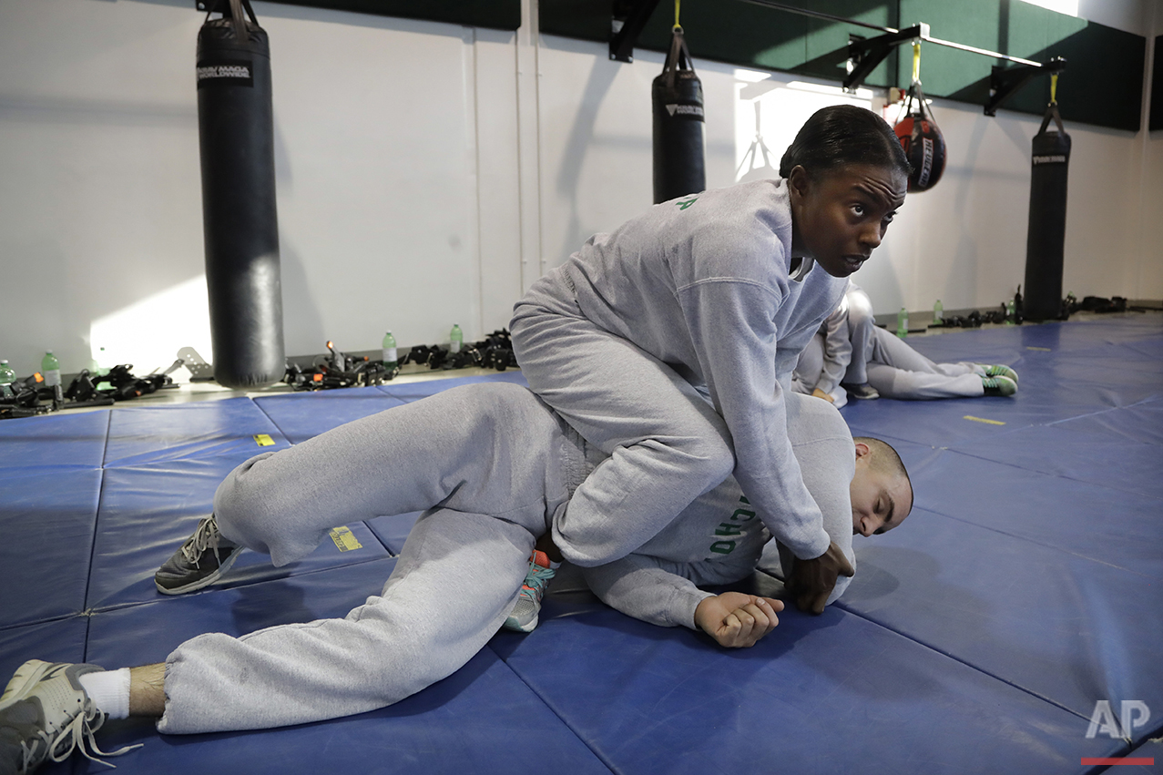 In this Friday, July 29, 2016 photo, Los Angeles County sheriff's deputy recruit Renata Phillip, top, trains with Robert Nichols during a defensive tactics class at the Biscailuz Regional Training Center in Monterey Park, Calif. (AP Photo/Jae C. Hong)