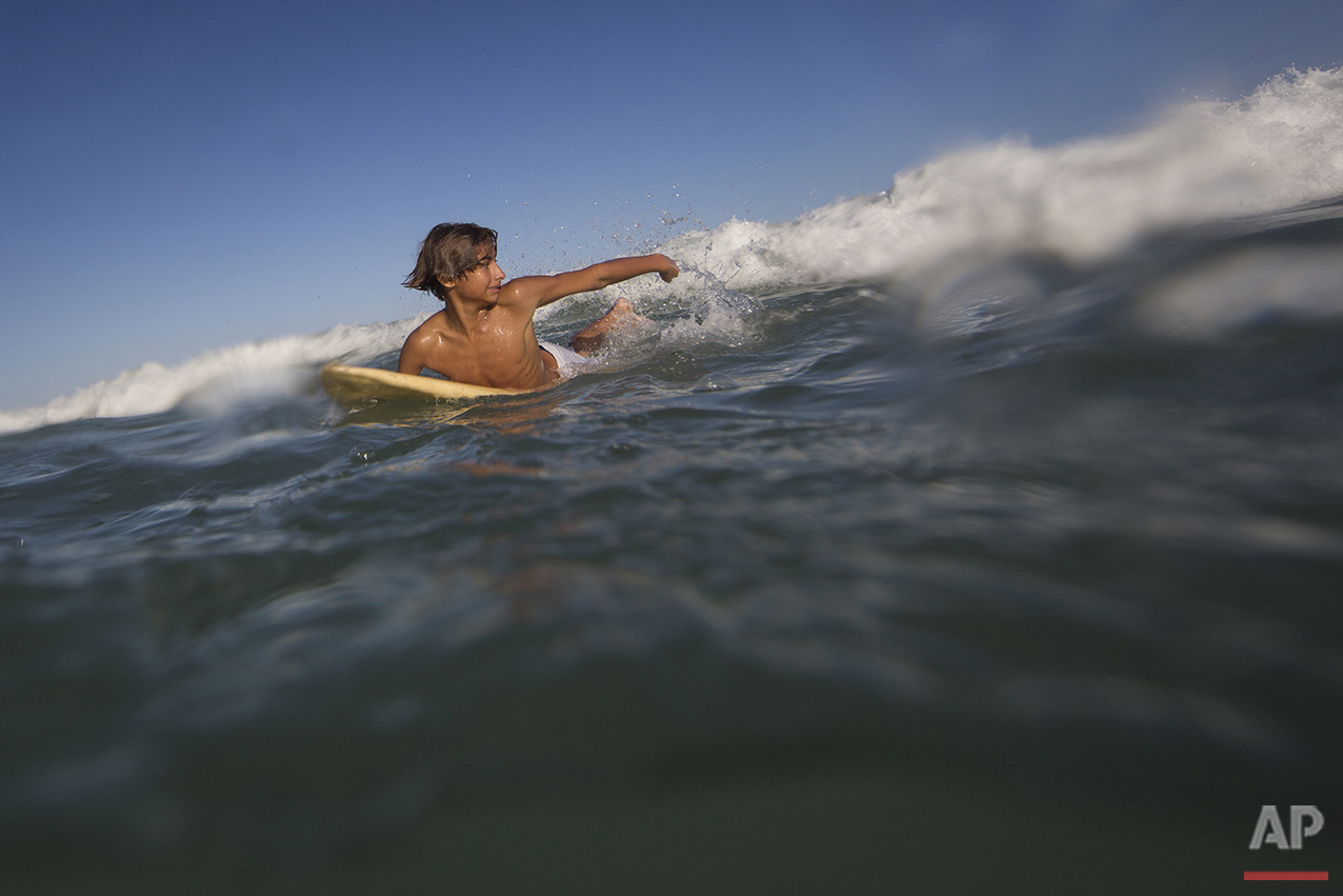 "Eric Marques paddles to catch a wave during his surfing class off Sao Conrado beach in Rio de Janeiro, Brazil, Saturday, Aug. 13, 2016. ""I love surfing. I love being in the water. There's not much for us to do at home,"" said Marques, who lives with his grandmother in a shack on the hillside next to a fetid cascade of raw sewage. We have a lot of gunfights (in Rocinha). It's hard to live there. It's too crowded, so I prefer to hit the beach."" (AP Photo/Felipe Dana)"