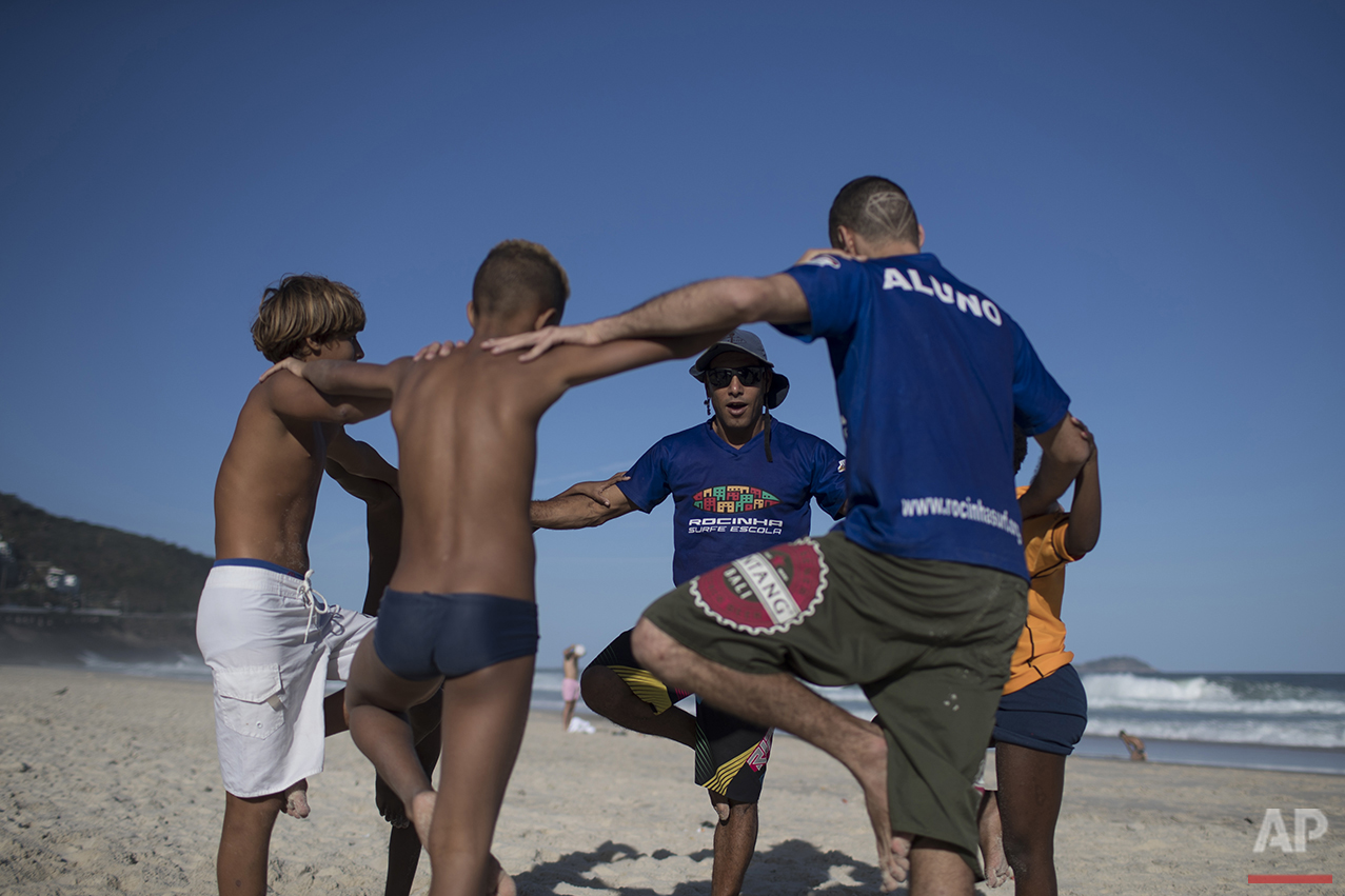 "Ricardo Ramos, center, founder of Rocinha Surf School, exercises with his students during a class on Sao Conrado beach in Rio de Janeiro, Brazil, Saturday, Aug. 13, 2016. In the favela, Ramos used to sell hot-air balloons filled with fireworks to drug dealers who used them to celebrate birthdays or when one of their own was released from jail. Then, he began surfing and decided that he wanted to give back to his community. ""Their communities have been abandoned for decades,"" Ramos said. ""When they go home, they face the troubles of their lives."" (AP Photo/Felipe Dana)"