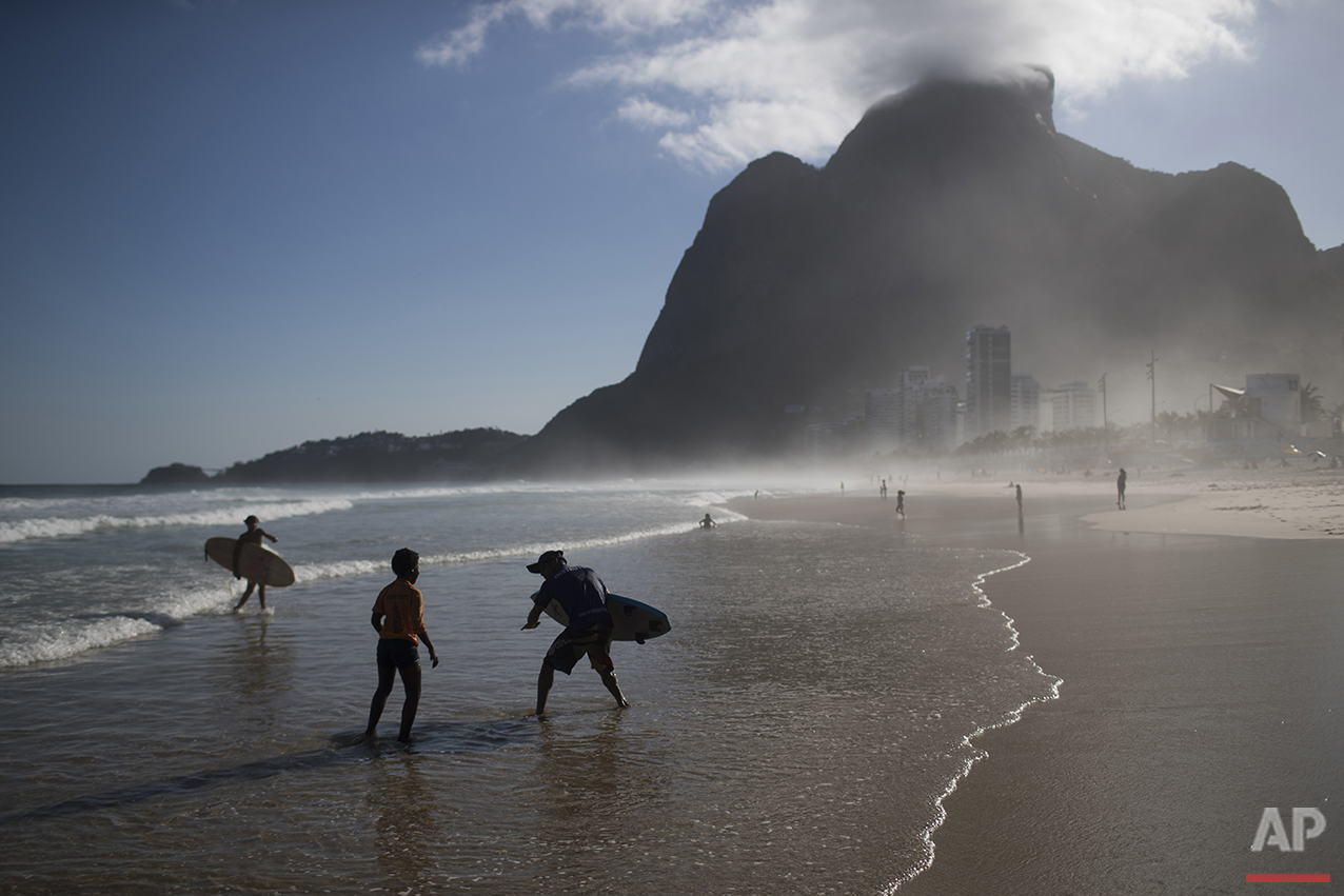 "Ricardo Ramos, third from left, founder of Rocinha Surf School, gives a surfing class to children on Sao Conrado beach in Rio de Janeiro, Brazil, Saturday, Aug. 13, 2016. ""The kids often get mycosis, white spots on their skins,"" Ramos said about his students who surf without a bodysuit and just wear board shorts. ""But there's nothing we can do about it and they've built antivirus. Favela surf has no luxuries."" (AP Photo/Felipe Dana)"