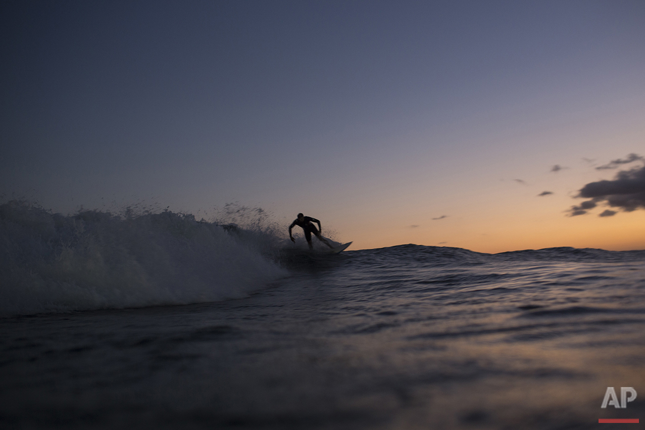 A man surfs during sunset off Arpoador beach in Rio de Janeiro, Brazil, Saturday, Aug. 13, 2016. This month, the IOC included surfing in its Olympic program for the Tokyo Games in 2020. (AP Photo/Felipe Dana)