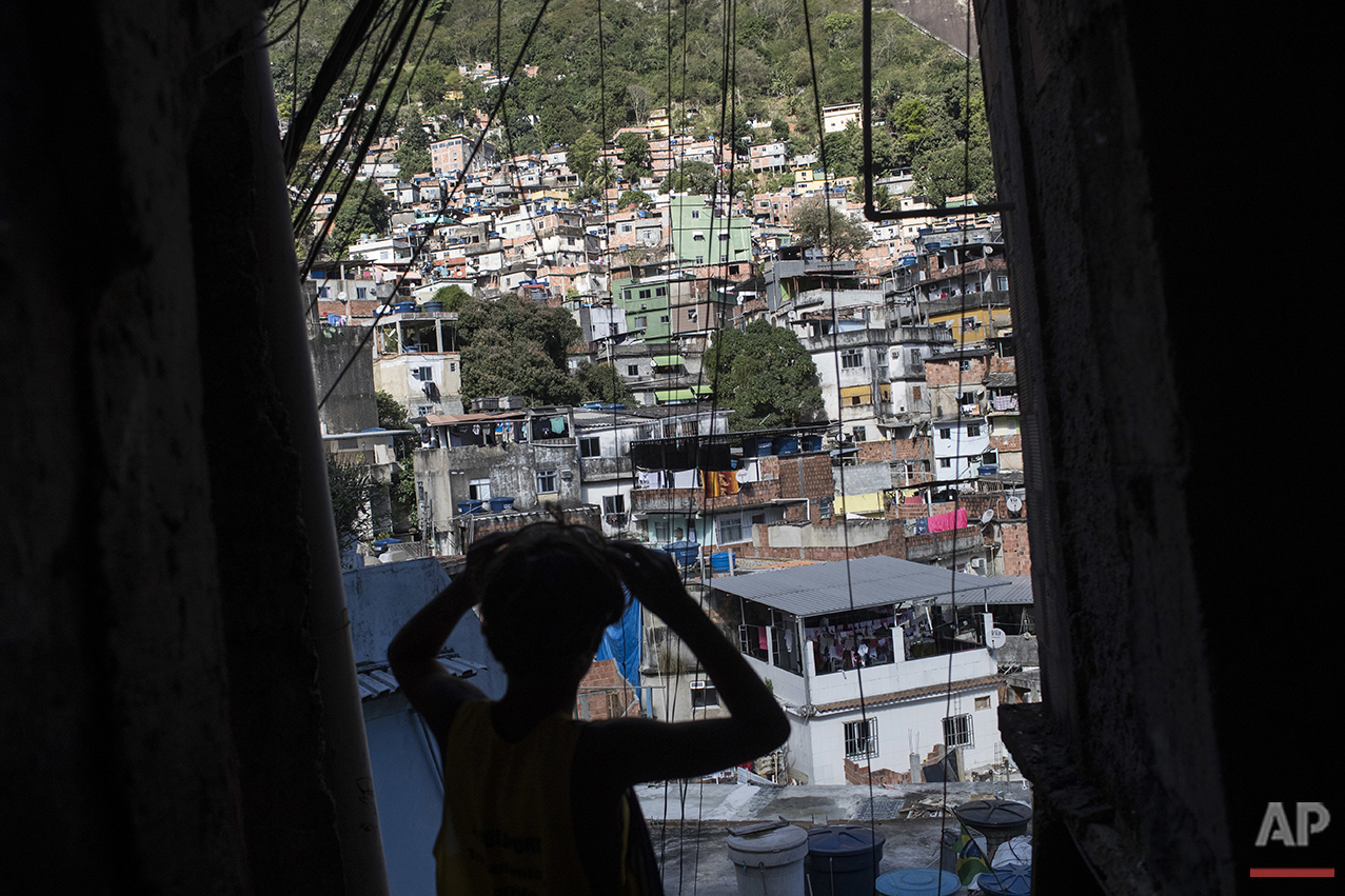 Eric Marques adjusts his sunglasses as he walks down the Rocinha slum on his way to surf at the nearby Sao Conrado beach in Rio de Janeiro, Brazil, Saturday, Aug. 13, 2016. The children of Rio de Janeiro's biggest slum have little. But they border the water. While some of the world's top Olympic athletes compete in nearby Guanabara Bay, they attend a surfing school in the heavily polluted waves and dream that maybe, they'll be good enough to compete on their sport's biggest stage one day. (AP Photo/Felipe Dana)